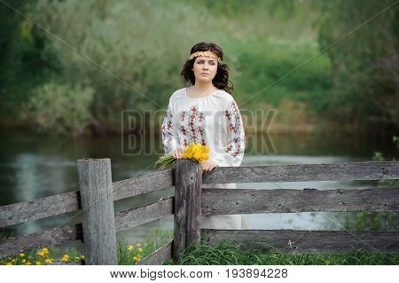 Portrait of a beautiful girl in Slavic clothes. Young woman with a bouquet of dandelions. Summertime
