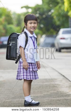portrait of asian children wearing student uniform carrying school backpack toothy smiling face