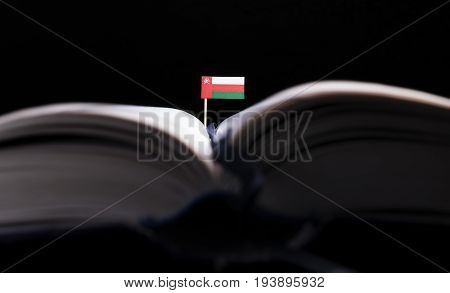 Omani Flag In The Middle Of The Book. Knowledge And Education Concept.