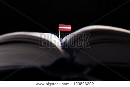 Latvian Flag In The Middle Of The Book. Knowledge And Education Concept.