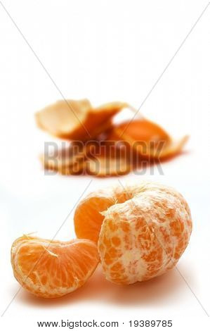 Peeled mandarine with the peel in the background. Isolated