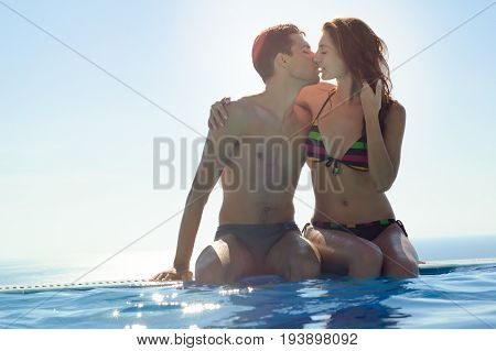 Young Couple Kissing in an Infinity Swimming Pool. Honeymoon Couple at Luxury Resort. Romantic Summer Vacation.