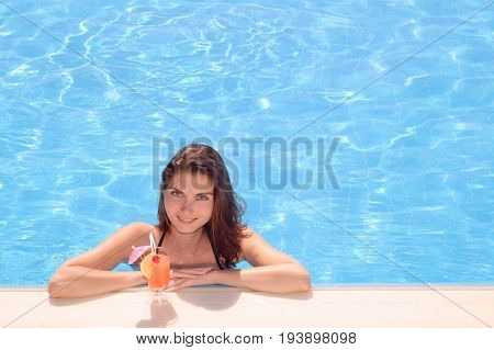 Young Beautiful Woman Relaxing by the Swimming Pool with Cold Exotic Cocktail. Summer Vacation.