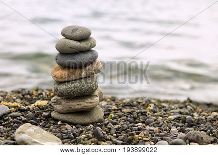 Stack of zen stones on beach. Pyramid of stones on the beach. Zen meditation background - balanced stones stack close up.