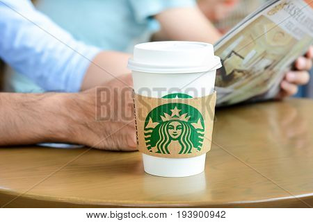 Bangkok Thailand - May 20 2015 : Starbucks coffee cup on the table with a man reading newspaper as background in Starbucks coffee shop.