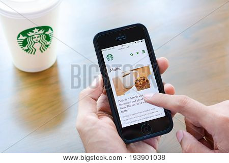 Bangkok Thailand - May 20 2015 : Hand holding smart phone opening online menu web page of Starbucks with Starbucks coffee cup on the table.
