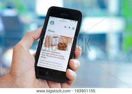Bangkok Thailand - May 20 2015 : A man hand holding iphone with Starbucks menu web page on screen