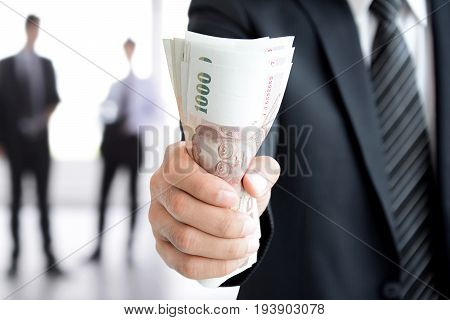 Businessman hand gripping money Thai Baht (THB) bills - investment success and profitable business concepts