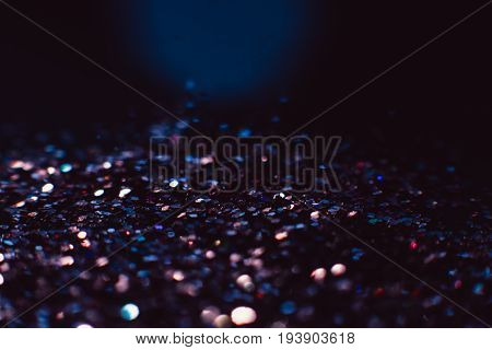 Abstract shining glitters dark violet holiday bokeh background with copy space. Defocused lights dramatical backdrop. Christmas and New Year wallpaper decorations concept.