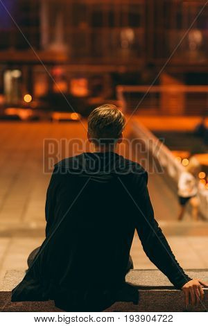Guy sitting in night street, back view. Rear of man having rest at city street at square, dreaming about something, free space