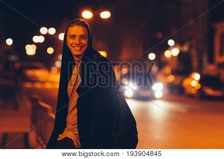 Young happy handsome casual student in hood outdoors. Portrait of hooded guy walking through night city
