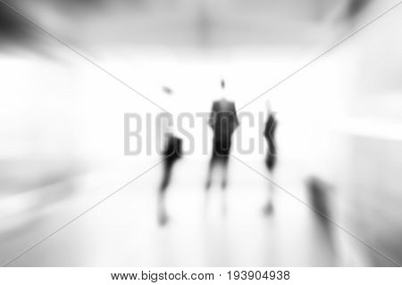 Blur monocrome abstract background of business people standing in building hall
