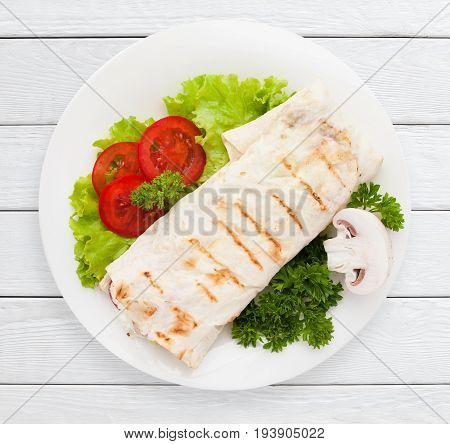 Shawarma. Sandwich wrap of pita bread on plate top view. Healthy food, served fast food, lunch dish concept. White wooden planks background.