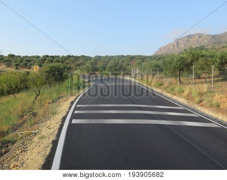 Newly painted white road markings on rural tarmacked road in Andalusia Spain