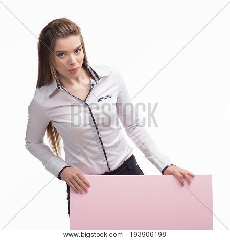 Young pry woman portrait of a confident businesswoman showing presentation, pointing placard pink background. Ideal for banners, registration forms, presentation, landings, presenting concept..