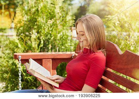 Summertime And Leisure Concept. Sideways Portrait Of Attractive Schoolgirl Wearing Red Sweater Readi