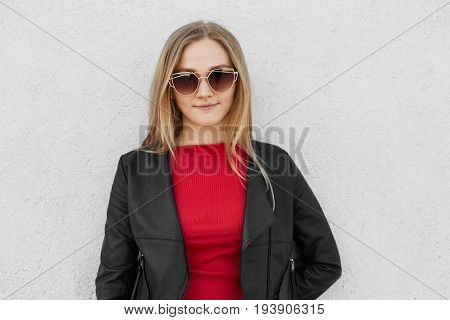 Portrait Of Fair-haired Female Wearing Sunglasses, Red Sweater And Black Leather Jacket Posing Again