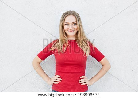 Waist Up Portrait Of Blonde Female In Red Clothes Standing Against White Background Holding Hands On