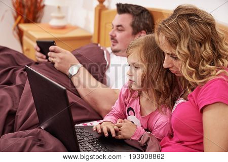 Close up shot of family using digital devices while lying in bed in the morning
