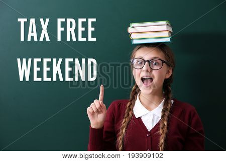 Girl with books on head standing near school blackboard. Text TAX FREE WEEKEND on background