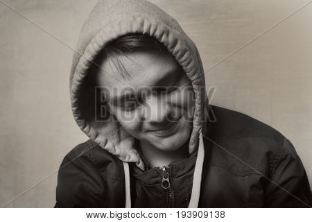 Vintage style close-up portrait. A teenager in a hood.