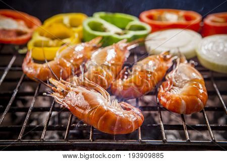shrimpprawns grilled with chilly and onion on barbecue stove