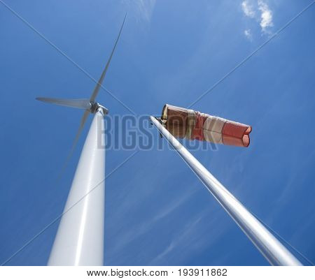 red and white windbag and wind turbine against background of blue sky