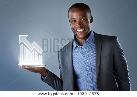 Smiling african businessman in suit showing virtual holographic display of up trend bull market