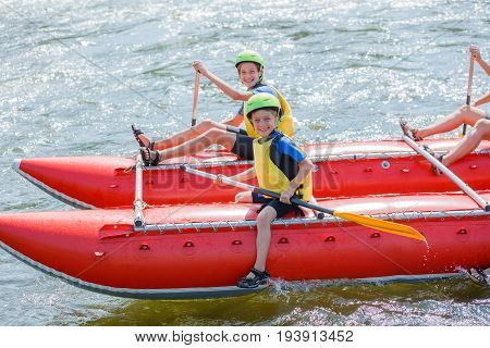 Cute boy in helmet and with paddle ready for rafting on the catamaran with his sister