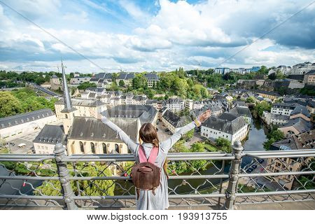 Young female traveler enjoying beautiful cityscape view on the old town in Luxembourg city
