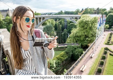 Young female traveler with photocamera enjoying beautiful cityscape view on the green valley with bridge and garden in Luxembourg city