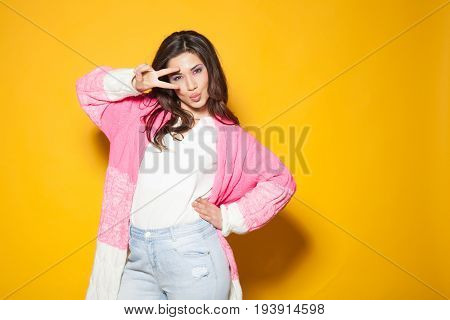 the girl in the pink jacket shows two fingers on a yellow background