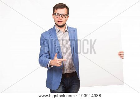 Young enlivened man portrait of a confident businessman showing presentation, pointing paper placard gray background. Ideal for banners, registration forms, presentation, landings, presenting concept.