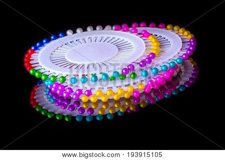 Circle bed of colorful sewing straight pins on black background with reflection close-up