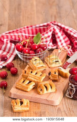 Cherry pastry pies with jam on cutting board.