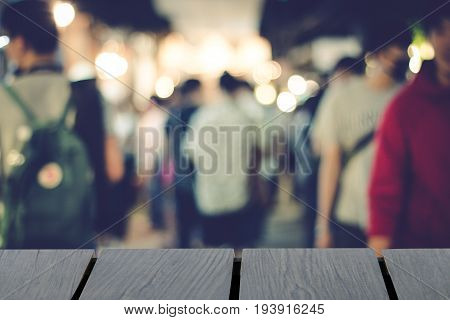 Blurred people walking background and wooden table on font. mock up