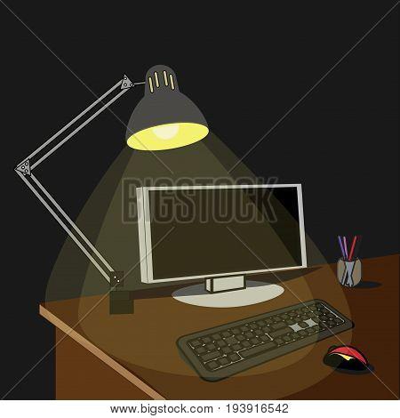 Lamp illuminated desktop with computer at night