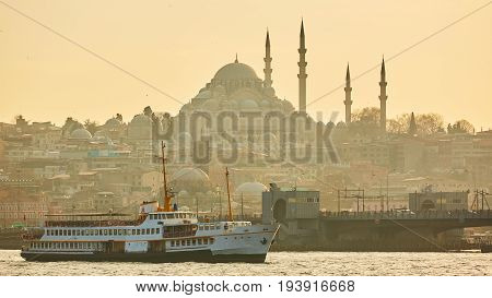 Tourist boat sails on the Golden Horn in Istanbul at sunset, Turkey