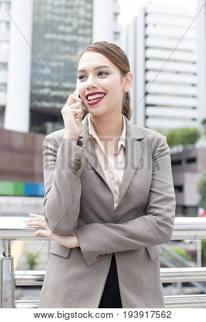 Young Asian Businesswoman Using Smartphone For Talking With Attractive Smiling At City Backgroung,