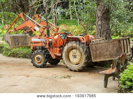 Orange tractor with a trailer and large wheels.