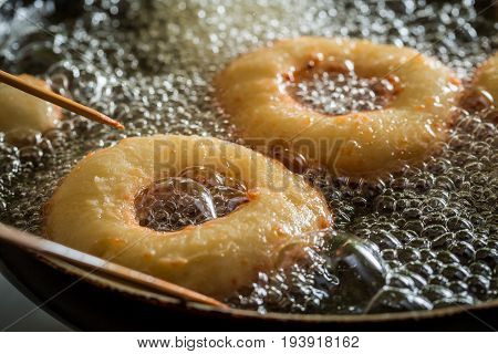 Frying Sweet And Tasty Donuts On Hot Oil