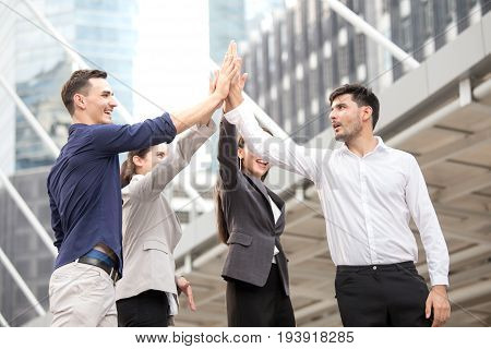 Businesspeople Rise Hand Together With Happy Emotion At Outdoor Place, Business Teamwork Concept.