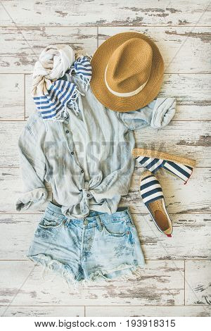 Summer outfit flatlay. Pastel coloured summer women's clothes, parquet background, top view. Blue shorts, linen shirt, straw hat, yellow bag, sunglasses, striped neckerchief, espadrillas