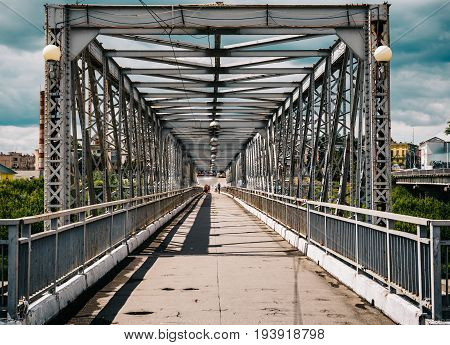 Old urban metal bridge in sunny day, perspective lines, toned