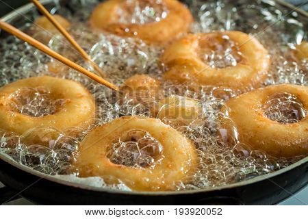 Frying Sweet And Tasty Donuts On Fresh Oil