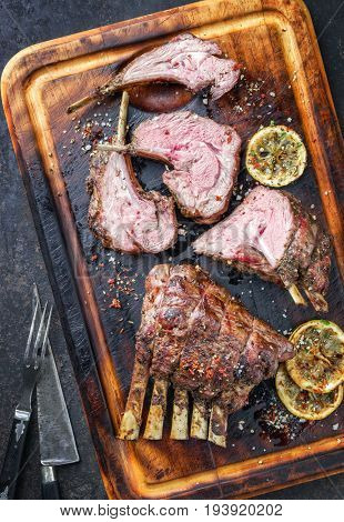 Barbecue Leg of Lamb and Rack as top view on burnt cutting board