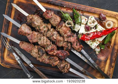Traditional Greek Souvlaki with Feta and Vegetable as top view on an old burnt cutting board