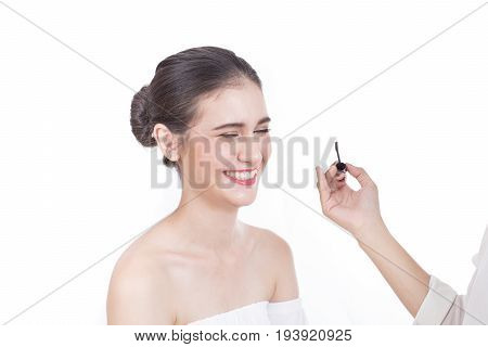 Professional Asian Akeup Artist Applies Eyeliner, Beautiful Woman Face With Attractive Smile. Perfec