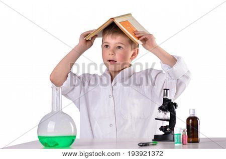 Bewildered scientist boy with book on his had on white background in the lab