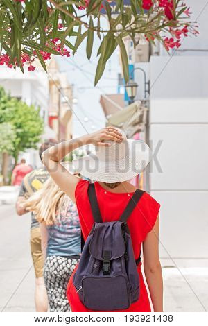 Woman in red dress, white hat and backpack walking in town, windy day